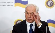 Ukraine's former Prime Minister Mykola Azarov adjusts his glasses as he attends a news conference in Moscow, Russia, August 3, 2015