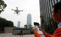 An employee from DJI Technology Co. demonstrates the remote flying with his Phantom 2 Vision+ drone in Shenzhen, south China's Guangdong province.