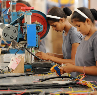 Indian women work at the electrical wiring section of the OREVA E Bike manufacturing facility near Samakhiali of Kutch district, some 240 kms from Ahmedabad on May 24, 2012