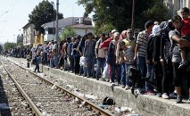 Migrants line up to board a train that would take them towards Serbia, at the railway station in the southern Macedonian town of Gevgelija, on Monday, Aug. 17, 2015