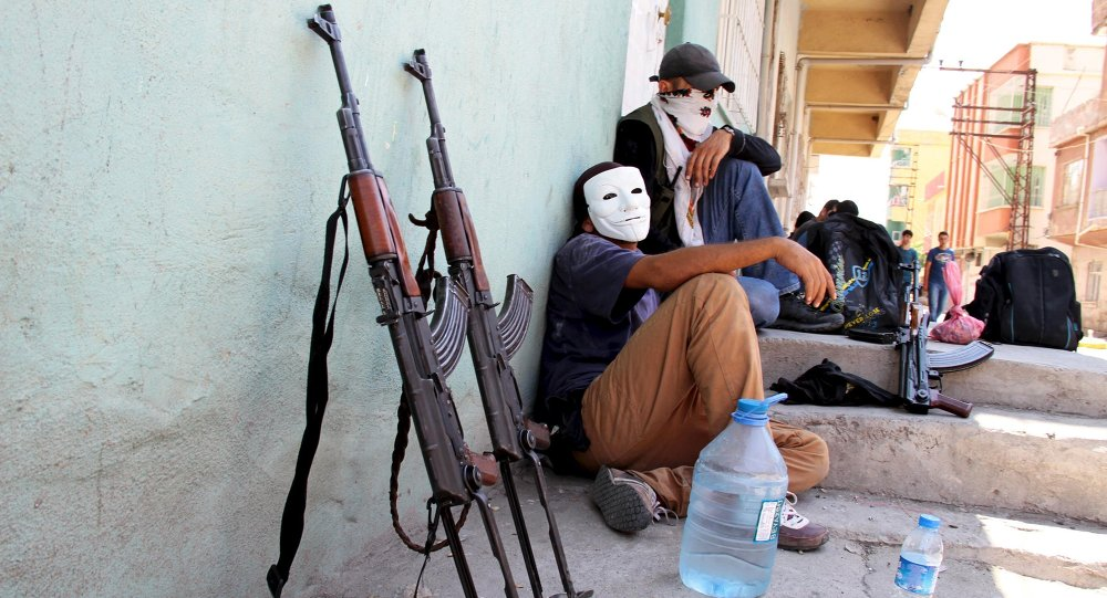 Masked members of YDG-H, youth wing of the outlawed Kurdistan Workers Party (PKK), sit next to their weapons in Silvan, near the southeastern city of Diyarbakir, Turkey, August 17, 2015