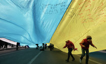 Ukrainian kids play under a huge yellow-and-blue Ukrainian national flag at a rally in Kiev's Independent square, Ukraine, Saturday, April 5, 2014
