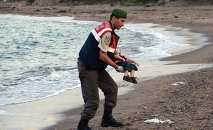 A paramilitary police officer carries the lifeless body of an unidentified migrant child, lifting it from the sea shore, near the Turkish resort of Bodrum, Turkey, early Wednesday, Sept. 2, 2015.
