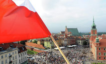A Polish national flag waves above the Zamkowy Square as people stop to commemorate the 70th anniversary of the 1944 Warsaw Uprising, in Warsaw, Poland, Friday, Aug. 1, 2014