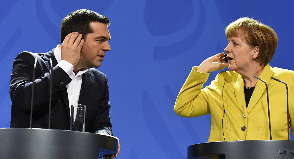 German Chancellor Angela Merkel (R) and Greek Prime Minister Alexis Tsipras hold their earpieces as they address a press conference following talks at the chancellery in Berlin, on March 23, 2015