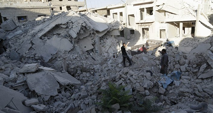 Residents inspect a site damaged by what activists said was a barrel bomb dropped by forces loyal to Syria's president Bashar Al-Assad in Maarat Al-Nouman, south of Idlib, Syria September 29, 2015