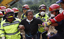 Rescue workers help a woman after she identified two family members as their bodies are retrieved from the site of a mudslide in Cambray, a neighborhood in the suburb of Santa Catarina Pinula, on the outskirts of Guatemala City, Saturday, Oct. 3, 2015.