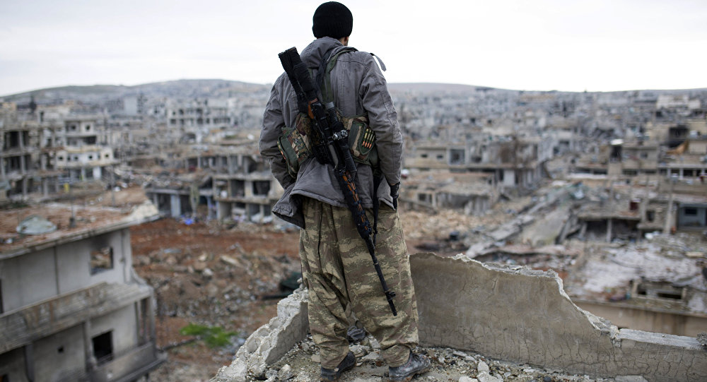 FILE - In this Jan. 30, 2015, file photo, a Syrian Kurdish sniper looks at the rubble in the Syrian city of Ain al-Arab, also known as Koban
