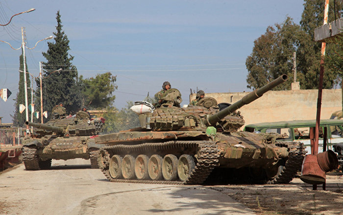 Syrian army tanks enter a village near the Kweyris military air base, in the east of the northern Syrian province of Aleppo, on November 15, 2015 after they took control of the surrounding villages from Islamic State (IS) group fighters
