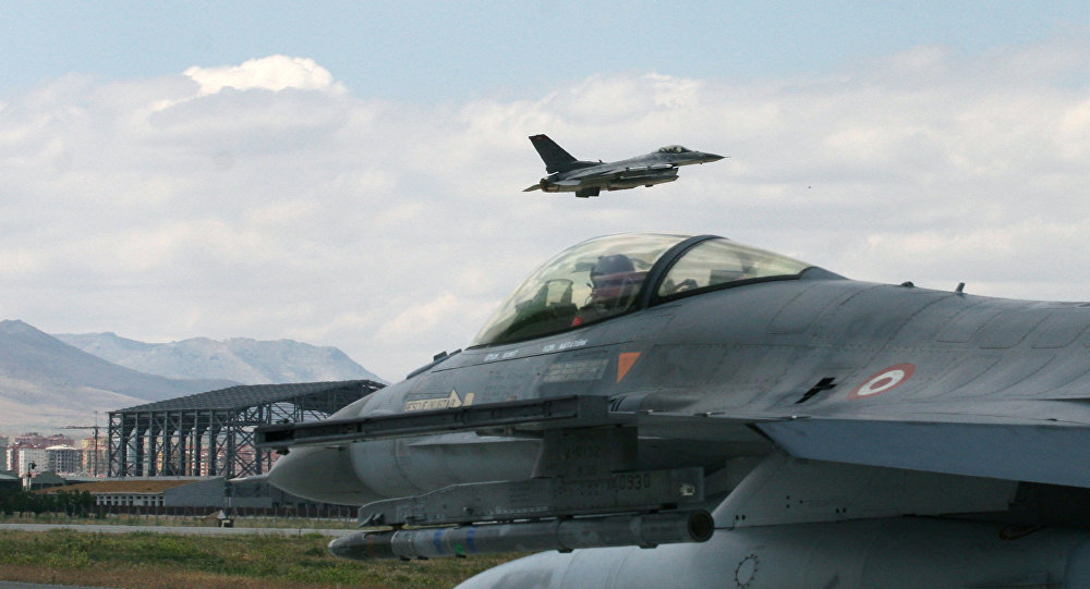 A Turkish F-16 prepares to taxi while another one takes off at 3rd Main Jet Air Base