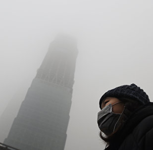 A woman waits for a bus below a skyscraper shrouded in smog on a heavily polluted day in Beijing on December 1, 2015.