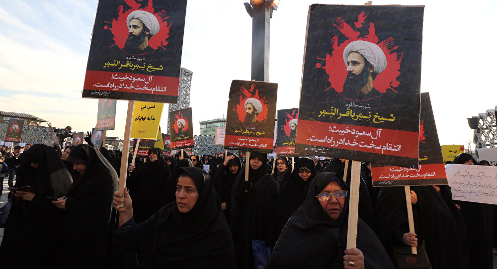 Iranian women gather during a demonstration against the execution of prominent Shiite Muslim cleric Nimr al-Nimr (portrait) by Saudi authorities, at Imam Hossein Square in the capital Tehran on January 4, 2016