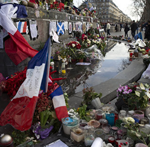 People stand next to the makeshift memorial in tribute to the victims of the Paris terror attacks, on January 4, 2016, at the Place de la Republique in Paris.