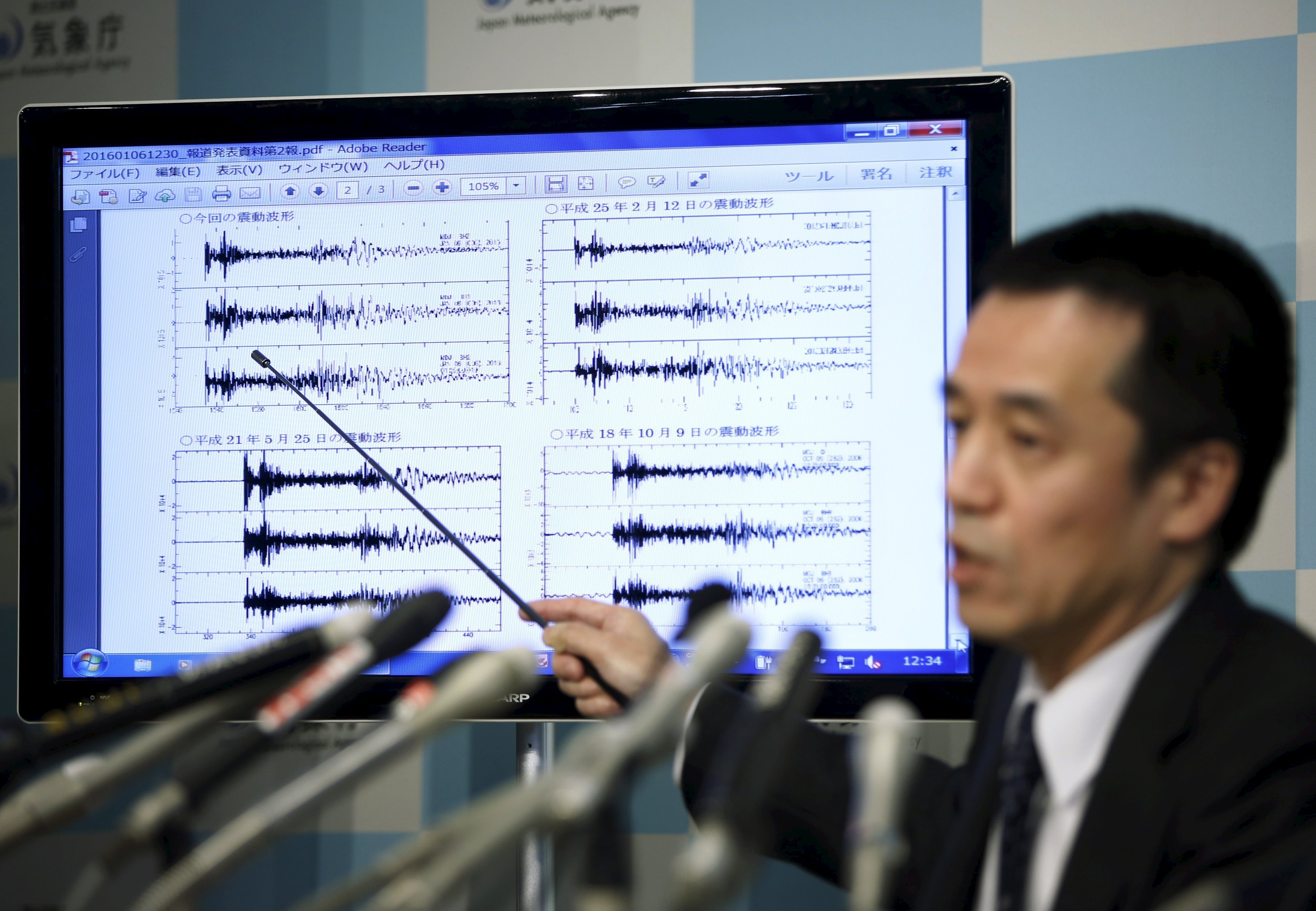 Hasegawa points at a graph of ground motion waveform data observed in Japan during a news conference at the Japan Meteorological Agency in Tokyo