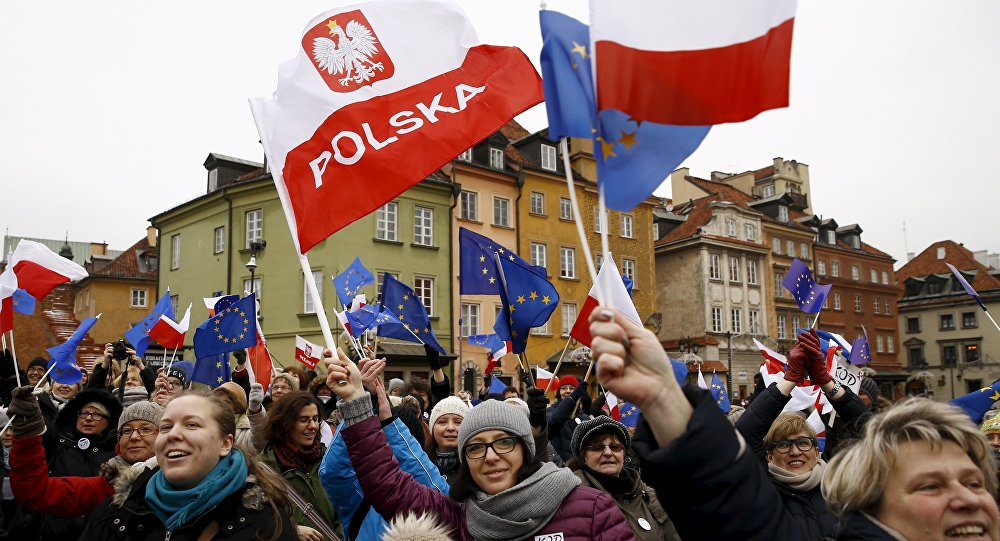 People hold EU and Polish flags as they gather during a pro-democracy demonstration at the Old Town in Warsaw, Poland January 9, 2016