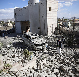 Men gather at the site of a house destroyed by Saudi-led airstrikes in Sanaa, Yemen, Friday, Jan. 8, 2016
