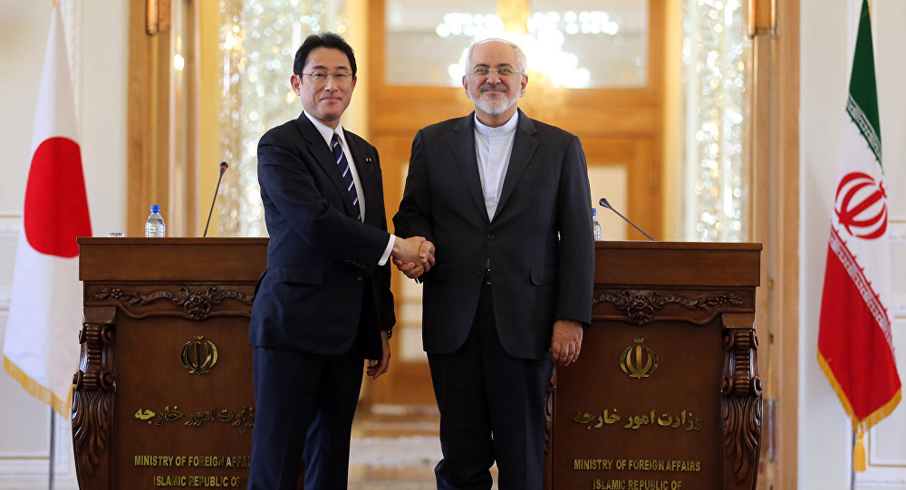 Iranian Foreign Minister Mohammad Javad Zarif (R) shakes hands with his Japanese counterpart, Fumio Kishida (Fille)
