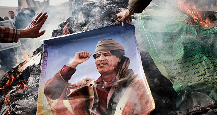 Benghazi residents burn portraits of Muammar Gaddafi, banners with his quotes and his Green Book