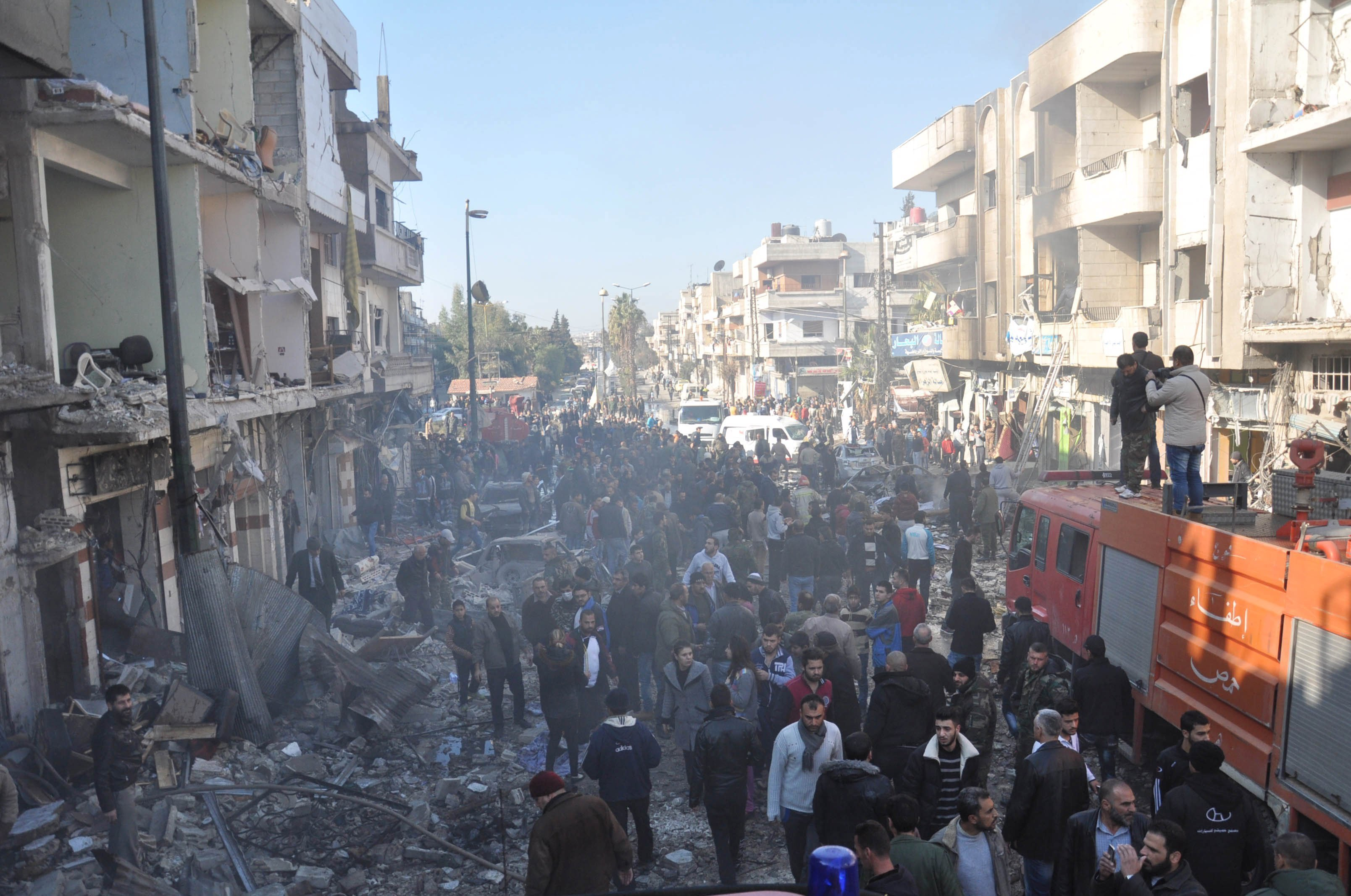 Syrian army soldiers, members of security services and civilians inspect the site of two bomb explosions in the Syrian city of Homs, Syria, in this handout picture provided by SANA on December 28, 2015