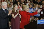 Former U.S. President Bill Clinton (L) applauds his wife, Democratic U.S. presidential candidate Hillary Clinton (R), as they appear with their daughter Chelsea (C) at Mrs. Clinton's caucus night rally in Des Moines, Iowa February 1, 2016