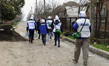 Monitors of the OSCE Special Monitoring Mission to Ukraine in Shirokine village, walk along a path on April 14, 2015 on the outskirts of the strategic port city of Mariupol