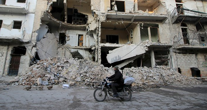 A man rides a motorcycle past damaged buildings in al-Myassar neighborhood of Aleppo, Syria January 31, 2016