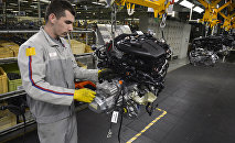 An employee works on the engine assembly line of the Peugeot 208 car by French car maker PSA Peugeot Citroen