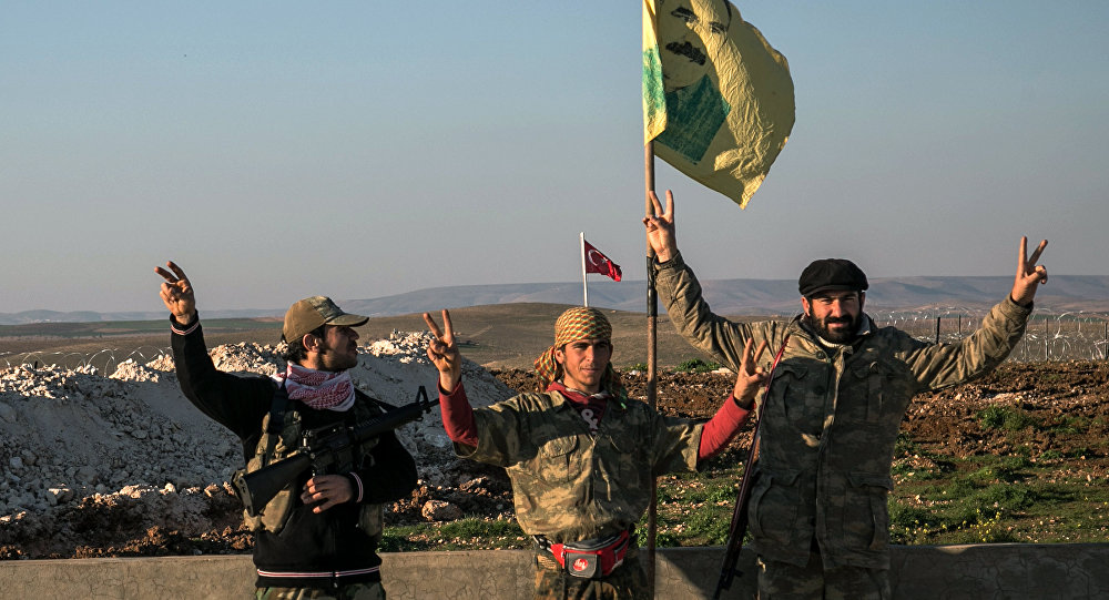 FILE - In this Sunday, Feb. 22, 2015, file photo, Syrian Kurdish militia members of YPG make a V-sign next to poster of Abdullah Ocalan, jailed Kurdish rebel leader, and a Turkish army tank in the background in Esme village in Aleppo province, Syria