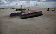In this Jan. 12, 2016 photo, a fisherman walks along the abandoned boats in the dried up Lake Poopo, on the outskirts of Untavi, Bolivia