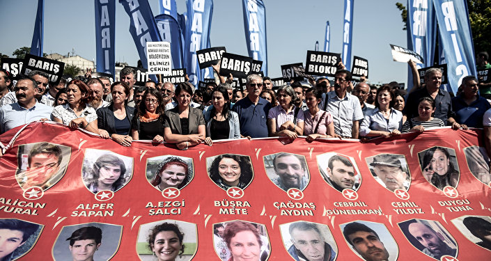 Protesters and members of Turkey's People's Democracy Party (HDP) hold a banner with pictures of the victims of the Suruc bomb attack after their peace march was banned by authorities in the Aksaray district of Istanbul on July 26