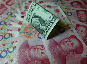 Yuan banknotes and US dollars are seen on a table in Yichang, central China's Hubei province on August 14, 2015