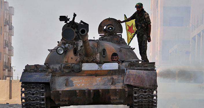 Fighters from the Kurdish People's Protection Units (YPG) drive a tank in the al-Zohour neighbourhood of northeastern Syrian city of Hasakeh (File)