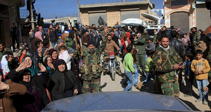 Residents of Nubul and al-Zahraa, along with forces loyal to Syria's President Bashar al-Assad, celebrate after the siege of their towns was broken, northern Aleppo countryside, Syria, in this handout picture provided by SANA on February 4, 2016