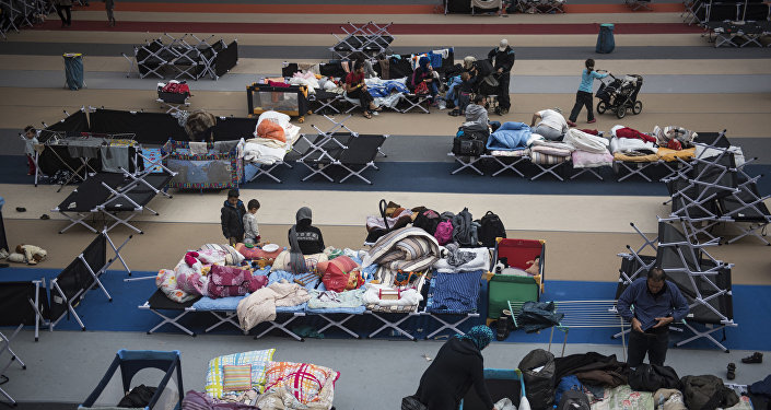 Immigrants rest on camp beds installed at the Horst Korber sports hall at the Berlin Olympic stadium complex Olympiapark on October 23, 2015