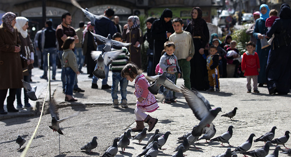 A Syrian girl chases pigeons in Marjeh Square, in Damascus, Syria, Saturday, February 27, 2016.