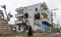 A woman walks past the ruins of a building as curfew ends during daylight in the town of Silopi. (File)