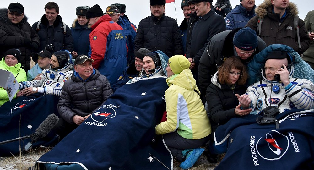 US astronaut Scott Kelly (R) and Russian cosmonauts Sergei Volkov (C) and Mikhail Korniyenko, surrounded by ground personnel, rest shortly after landing near the town of Dzhezkazgan (Zhezkazgan), Kazakhstan, March 2, 2016.