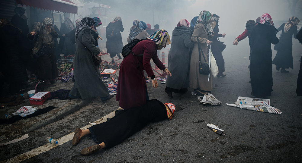 Women helps another woman who felt as Turkish anti-riot police officers launch tear gas to disperse supporters in front of the headquarters of the Turkish daily newspaper Zaman in Istanbul on March 5, 2016, after Turkish authorities seized the headquarters in a midnight raid