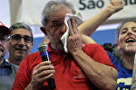 Brazilian former president Luiz Inacio Lula da Silva (C) wipes tears as he attends a meeting organized by unionists and members of the Workers Party (PT) in Sao Paulo downtown Brazil on March 4, 2016. Brazil's powerful Lula da Silva lashed out at prosecutors Friday after he was briefly detained by police as part of a probe into a massive corruption scheme