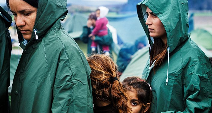 Migrants queue for a food distribution under the rain on March 10, 2016, in a makeshift camp at the Greek-Macedonian border, near the Greek village of Idomeni.