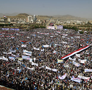 Yemenis wave national flags and hold placards during a protest against the Saudi-led coalition, commemorating one year of the alliance's military campaign against insurgents on March 26, 2016 next to the Monument to the Unknown Soldier in the Yemeni capital Sanaa