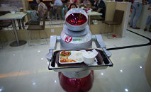 This photo taken on August 13, 2014, shows a robot carrying food to customers in a restaurant in Kunshan. It's more teatime than Terminator -- a restaurant in China is electrifying customers by using more than a dozen robots to cook and deliver food