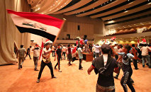 Iraqi protesters wave national flags as they gather inside the parliament after breaking into Baghdad's heavily fortified Green Zone on April 30, 2016