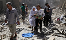 A Syrian family walks amid the rubble of destroyed buildings following a reported airstrike on April 28, 2016 in the Bustan al-Qasr rebel-held district of the northern Syrian city of Aleppo