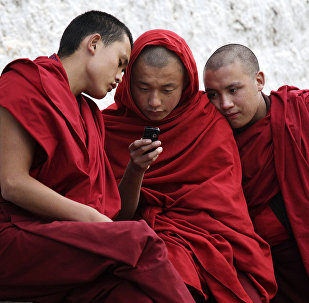 Buddhist monks looking at a mobile phone