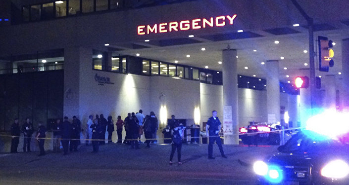 Police and others gather at the emergency entrance to Baylor Medical Center in Dallas, where several police officers were taken after shootings Thursday, July 7, 2016.