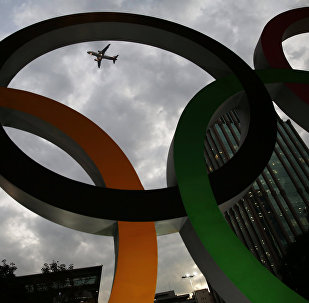 An airplane flies past Olympic rings placed at the entrance of office building ahead of the Rio 2016 Olympic Games, in Sao Paulo, Brazil, July 19, 2016