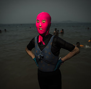 A woman wearing a facekini poses at the beach in Qingdao, eastern China's Shandong province