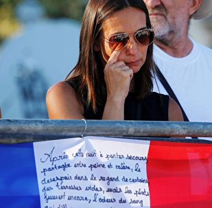A woman reacts near flowers and flags placed in tribute to victims, two days after an attack by the driver of a heavy truck who ran into a crowd on Bastille Day killing scores and injuring as many on the Promenade des Anglais, in Nice, France, July 16, 2016.