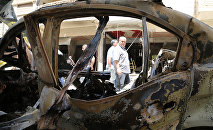 People walk past a burnt vehicle at the site of a suicide bombing suspected to have been carried out by the Islamic State (IS) group in the Christian Wusta neighbourhood of the divided Syrian northeastern city of Qamishli (File)